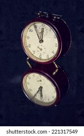 Filtered picture of a vintage alarm clock on a mirror background