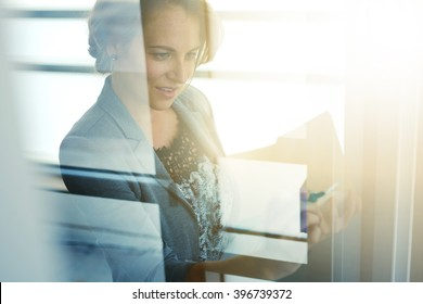 Filtered portrait of an executive business woman writing on a glass wall at sunset