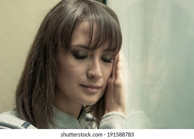 filtered, stylized colour image of moody woman face at window
