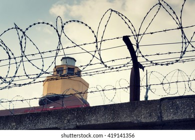 Filtered vintage guarding tower behind barbed wire fence prison walls