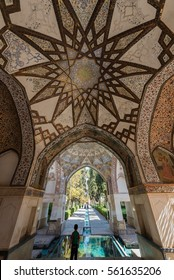 FIN, IRAN - 11 OCTOBER 2015: A boy looks into one of the fish ponds in the persian Fin Garden. Here the intricate ceiling decoration can be seen.