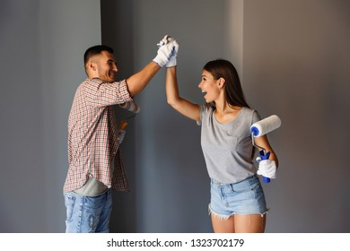 Final painting in the new house. Happy couple celebrating painting end with paint roller on grey wall background