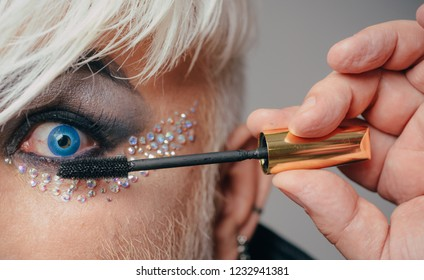 Final touch. Fashion male eye makeup. Transgender man apply mascara. Male makeup artist. Transgender man wear eyeshadows and eyebrow makeup. Male makeup look.