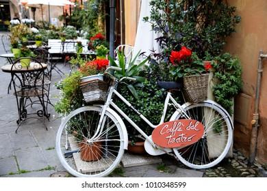 Finalborgo (SV), Italy - December 12, 2017: A white bicycle whith flowers in Finalborgo village, Finale Ligure, Liguria, Italy