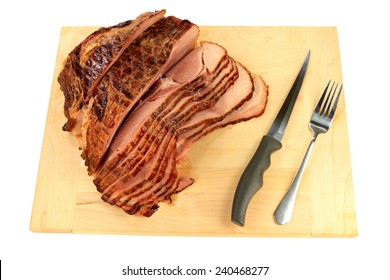 Finally backed pre cooked smocked Spiral-cut of Pork Ham over wooden cutting board ready to arrange American South Traditional New Year's Day meal on white background