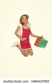 Finally bought it. Girl cute teenager carries shopping bag while jumping. Sale benefits. Kid bought clothing summer sale. Seasonal sale concept. Girls absolutely fond of shopping.