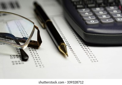 Finance analysis concept using finance report with pen, riding glasses and calculator
