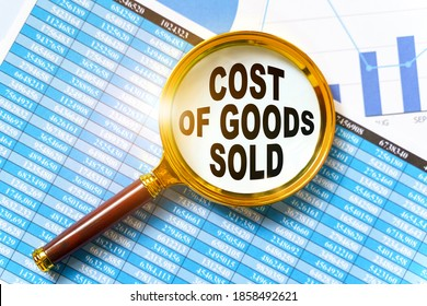 Finance and business concept. Financial reports, charts and a magnifying glass are on the table. Inside the magnifier there is an inscription - COST OF GOODS SOLD