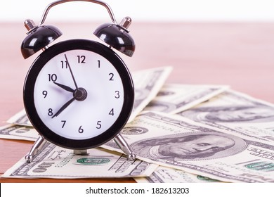Finance concept, alarm clock and one hundred dollar banknotes on wooden table.