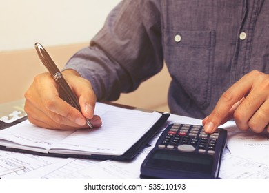 Finance concept. Businessman writing and make note about cost.