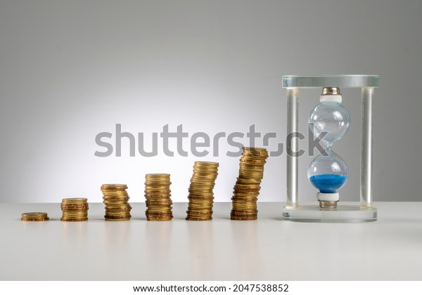 Finance Concept: Copy Space and arrangement of gold coin stack and hourglass sand timer
