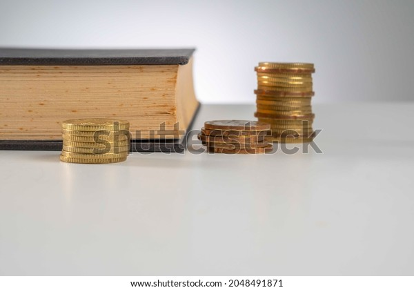 Finance Concept: Copy Space and arrangement of gold coin stack and old book