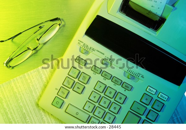 Finance Concept: day trader. Adding machine on newspaper business section.