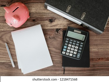 finance concept with file folder, note pad, calculator and piggy bank on table