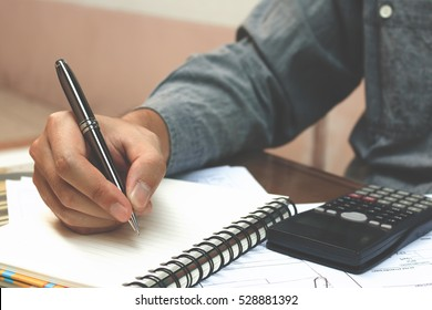Finance concept. Man writing and make note about cost.