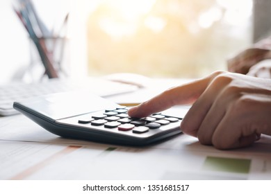 finance concept, Woman using calculator with analyze graph chart and computer laptop for profit forecast in the future.
