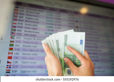 finance, currency conversion and people concept - hands with euro money over exchange rates on digital display screen