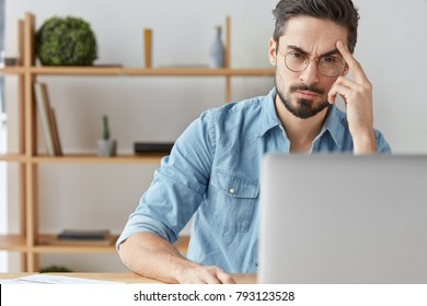 Finance director of big cooperation sits at home in his cabinet, reads financial report attentively, sits in front of opened laptop, has serious and concetrated look at screen, works online.