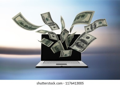 Finance and earning concept, one hundred dollar banknotes flying around laptop, internet, side view on dark background.