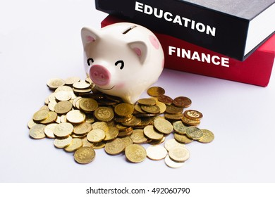 """""""Finance and Education"""" text on red and black books with happy pink piggy bank and gold coin near it on white background - finance, investment and saving concept"""