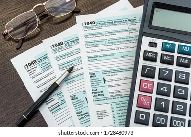 Finance income, time fot tax calculator and pen lying on federal form. Deadline