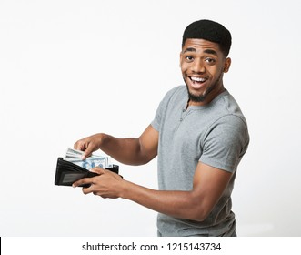 Finance, investment and money saving. Excited african-american man putting banknotes into wallet, white studio background
