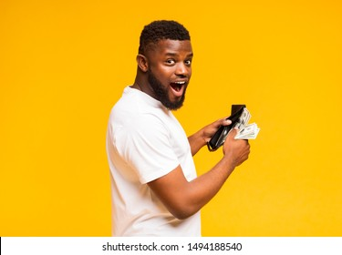 Finance, investment and money saving. Excited black man showing wallet full of dollars, free space