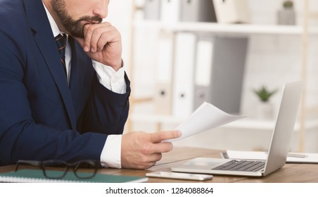 Finance manager working with documents and laptop, sitting on workplace in office, crop