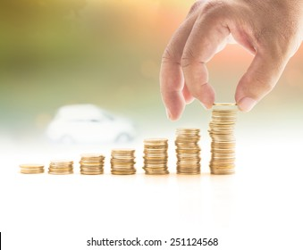 Finance payment plan concept: Human hand holding coin adding to stacks of golden coins on blurred vehicle on road sunset background