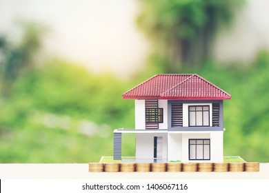 Finance, Stack of coins money and Model house on natural green background, Business investment and real estate
