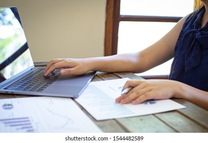 Finance, a young woman using a computer to analyze company revenue and expenses data to prepare for a meeting tomorrow