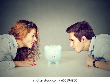 Finances in divorce concept. Wife and husband can not make settlement holding piggy bank sitting at table looking at each other with hatred