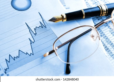 finances and economical background.Statistic, graphics and glasses in blue toned