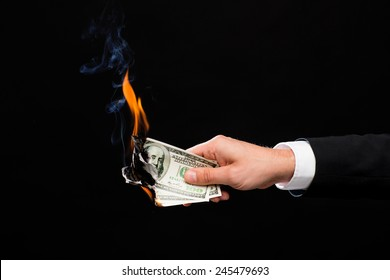 finances, people, savings and bankruptcy concept - close up of male hand holding burning dollar cash money over black background
