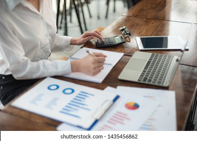 Financial and accounting concepts. Female businessmen use the calculator to calculate the profit of the business.