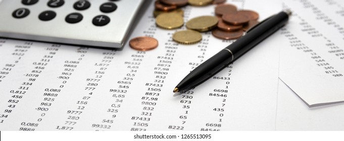 Financial accounting, Image a plurality of numbers on paper and calculator, Numbers on paper, a pen and a calculator, coins.