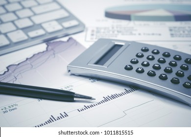 Financial accounting. Pen and calculator on stock market graphs and charts