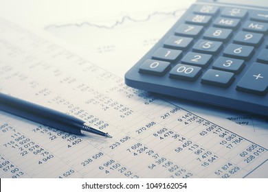 Financial accounting pen and calculator on balance sheets