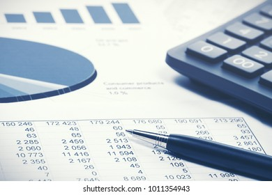 Financial accounting stock market graphs and charts. Pen and calculator on balance sheets