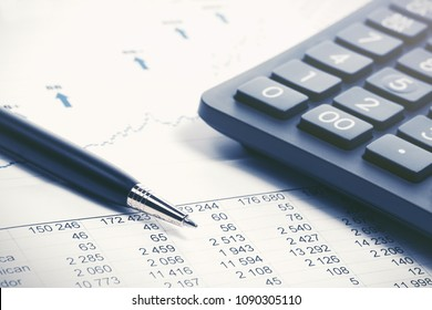Financial accounting stock market graphs and charts analysis pen and calculator on balance sheets