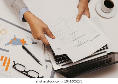 Financial adviser analyzing business papers and examining them. Businesswoman using laptop while working in office. Financial expert concept