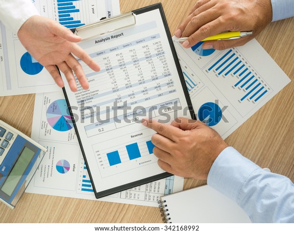 Financial adviser analyzing statistical data on desk in office. top view, above view.