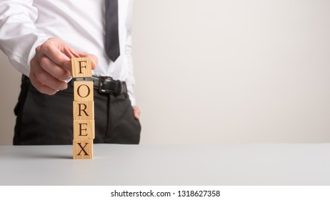 Financial adviser making a stack of wooden blocks spelling Forex with copy space to the right side of the image.