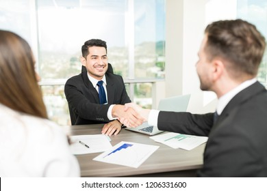 Financial adviser sealing a deal with clients at desk in office