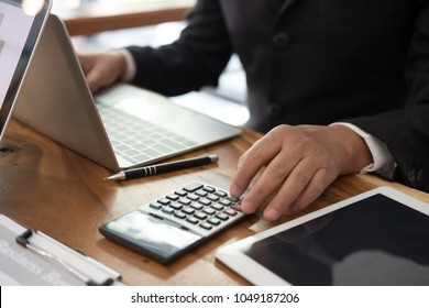 financial adviser working with calculator, business document & computer at office. accountant doing accounting & calculating revenue & budget. bookkeeper making calculation. finance & economy concept