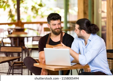 Financial advisor and cafe owner working in cafe.