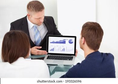 Financial advisor explaining investment plan to couple on laptop at office desk