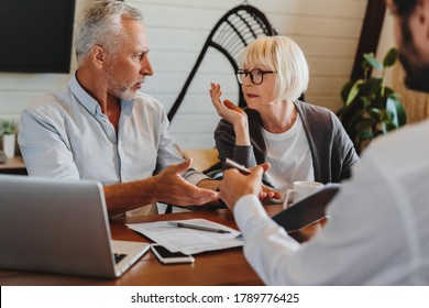 Financial advisor giving retirement advice to old couple while they arguing at home interior