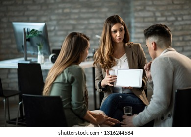 Financial advisor having a meeting with young couple and showing them their investment plans on touchpad. Copy space.