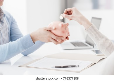 Financial advisor holding a piggy bank and customer inserting a coin: deposit, savings plan and retirement fund concept